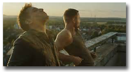 Movie still from Free Fall of two men standing on balcony overlooking city below