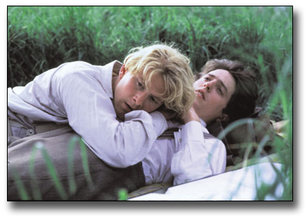 Scene from Maurice movie of two men lying in the grass on top of each other