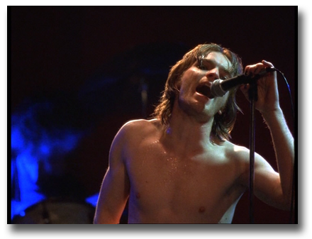 Scene from 'Velvet Goldmine' of Ewan McGregor singing at a concert