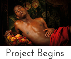"""Project Begins"" button - image of nude black man in red cloth with basket of fruit"