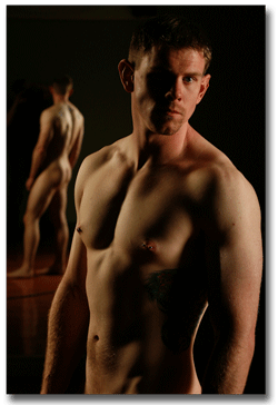 Nude man standing in front of a mirror so both sides of his naked body can be seen.