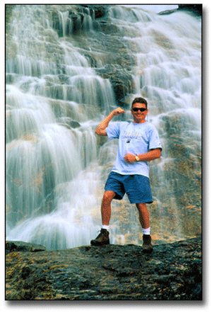 Terry Cyr standing at a waterfall in Montana flexing his muscle.