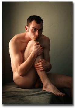 Man sitting naked in beautiful window light with his arms wrapped around his legs.