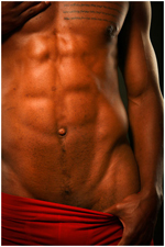 Torso detail of black male with ripped abs pulling down red shorts to expose his groin