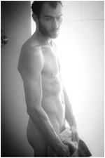 Black and white of a naked man standing in front of window holding towel with brilliant backlight